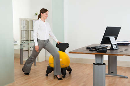 person standing: Young Happy Businesswoman Exercising With Pilates Ball On Chair In Office