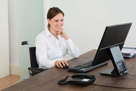 paraplegico: Feliz Empresaria que se sienta en silla de ruedas mientras que trabaja en equipo en el escritorio
