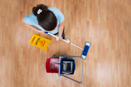 apartment cleaning: Woman With Cleaning Equipments And Wet Floor Sign Mopping Floor