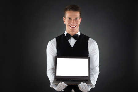 hospitality industry: Portrait Of Happy Waiter Showing Blank Display Laptop Stock Photo