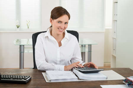 stack of papers: Photo Of Happy Businesswoman Calculating Invoice At Desk