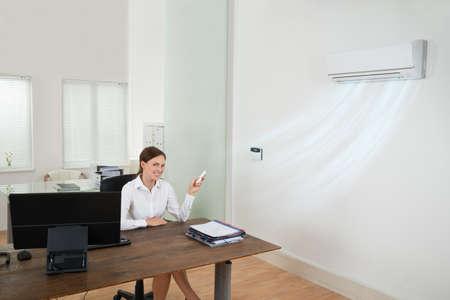 航空ショー: 幸せな実業家のオフィスでリモコン付きエアコンを動作