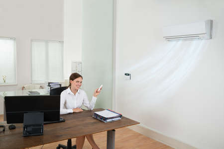Happy Businesswoman Operating Air Conditioner With Remote Control In Office Stock Photo