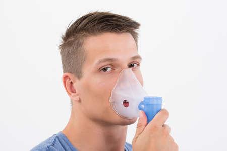 inhale: Portrait Of Young Man Inhaling Through Inhaler Mask