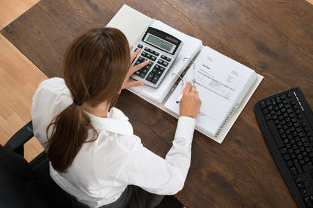 INVOICE: Young Businesswoman With Invoice And Calculator At Wooden Desk