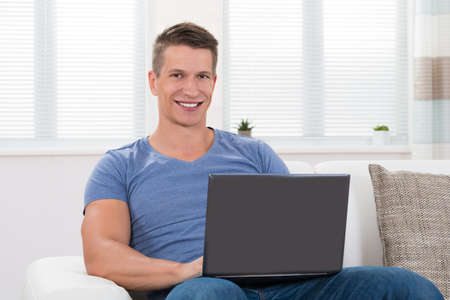 portables: Young Man Using Laptop While Sitting On Sofa