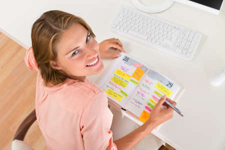 happy work: Young Happy Woman Making List Of Office Work In Diary