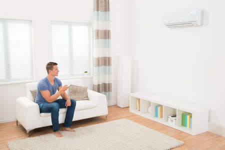home appliance: Young Man On Sofa Operating Air Conditioner With Remote Control Stock Photo