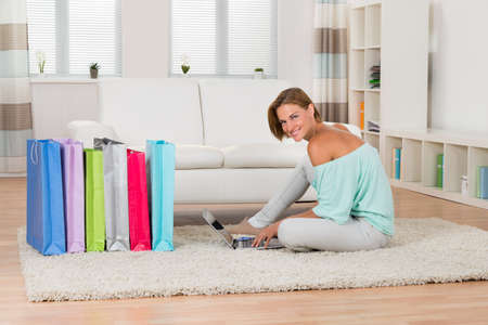 Young Woman Sitting On Carpet With Laptop And Shopping Bags In Living Room