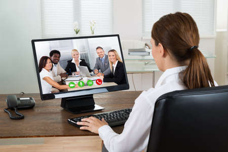 wireless woman work working: Young Businesswoman Videochatting With Colleagues On Computer In Office Stock Photo