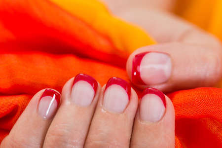 nailart: Close-up Of Woman Hands With Red Nail Varnish Holding Orange Fabric Stock Photo