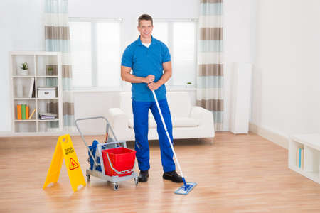 room service: Happy Worker With Cleaning Equipments And Wet Floor Sign In House