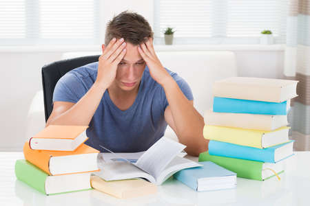 adult student: Portrait Of Tired Young Man Studying Books At Desk