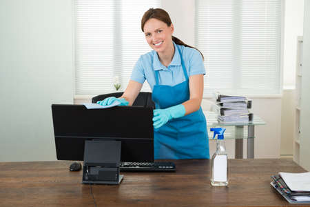 Young Woman In Workwear Rubbing Desktop Computer In Office Standard-Bild