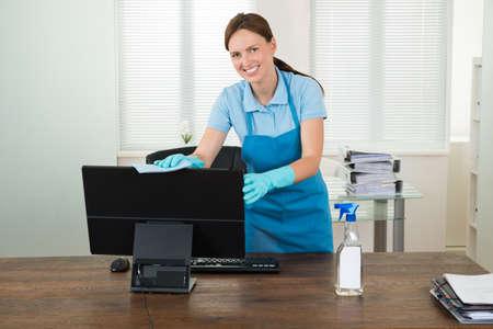 Young Woman In Workwear Rubbing Desktop Computer In Office Zdjęcie Seryjne - 45461068