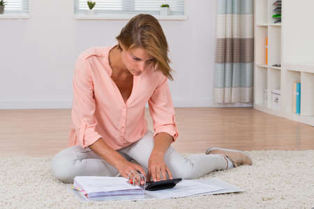 folder with documents: Young Woman Sitting On Carpet Calculating Invoices With Calculator