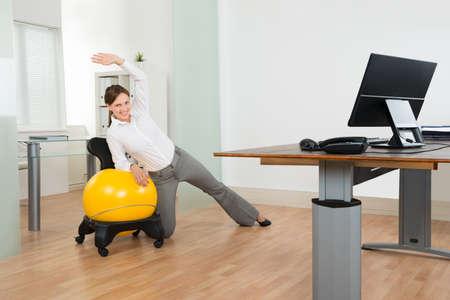 Jong blij zakenvrouw doet fitness oefening op Geel Pilates Bal In Office Stockfoto