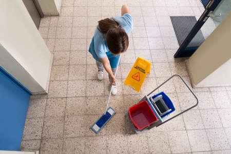 dweilen: Vrouwelijke Janitor Dweilen Vloer Met Reiniging apparatuur en Wet Floor Sign On Floor