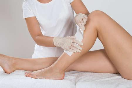 piernas: Esteticista Depilaci�n Pierna De La Mujer Con Cera Strip En la Cl�nica de Belleza