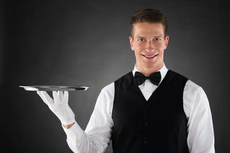 waiter serving: Young Waiter Holding Silver Tray In Hands