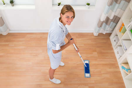 wood floor: Young Female Janitor Mopping Wooden Floor In House