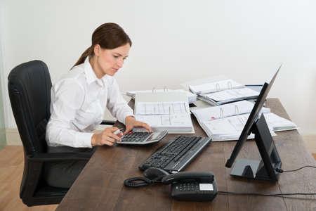 auditoria: Hembra Joven Contador Haciendo C�lculo Con la calculadora en el escritorio Foto de archivo