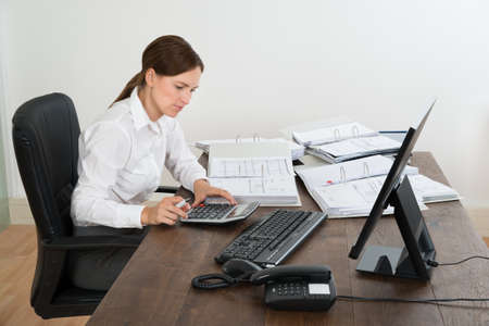 financial audit: Young Female Accountant Doing Calculation With Calculator At Desk Stock Photo