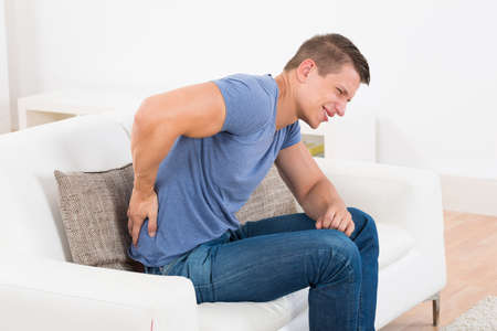 backpain: Young Man On Sofa Suffering From Backpain At Home Stock Photo