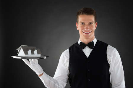 hospitality staff: Young Waiter Holding Tray With Small House Model Stock Photo