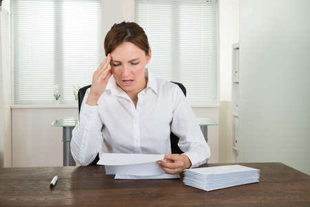 envelope: Stressed Businesswoman Looking At Document At Desk In Office