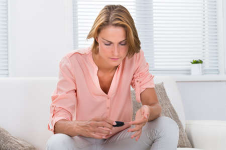 Young Woman Sitting On Sofa Checking Blood Sugar Level With Glucometer