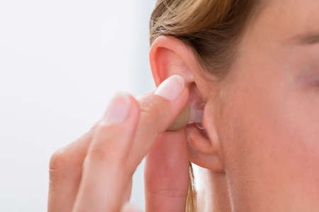 Close-up Of Female Hands Putting Hearing Aid In Ear