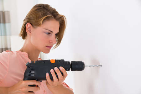 drill: Portrait Of Young Woman Making Hole In Wall With Drill Machine Stock Photo