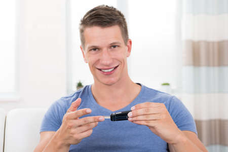 blood sugar level: Close-up Of Young Happy Man Checking Blood Sugar Level With Glucometer