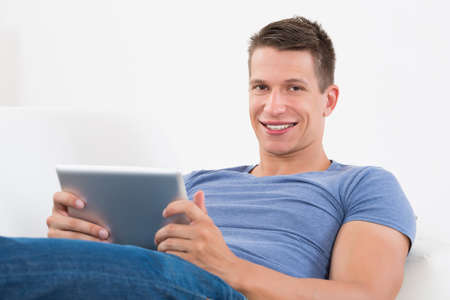 using tablet: Happy Man Looking At Digital Tablet While Lying On Sofa