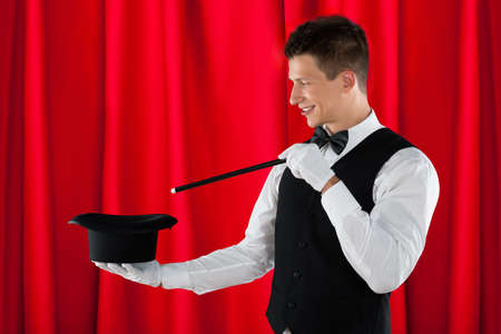 magician hat: Young Happy Magician With Magic Wand And Black Hat Stock Photo