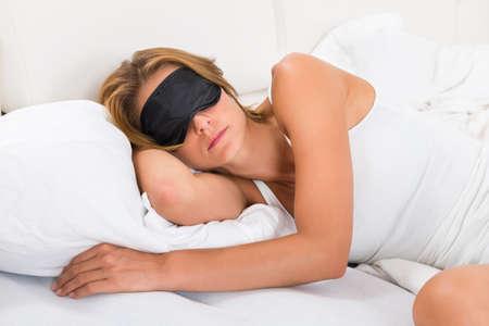 sleep mask: Young Woman Sleeping With Sleep Mask In Bed