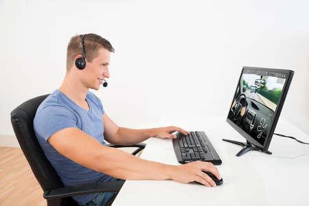 Szczęśliwy człowiek z słuchawki Playing Game na pulpicie komputera w domu