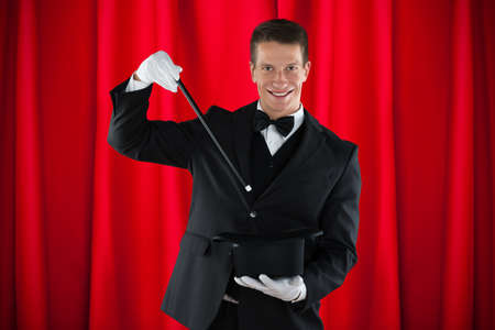 magic trick: Young Happy Magician Showing Magic Trick With Hat Stock Photo