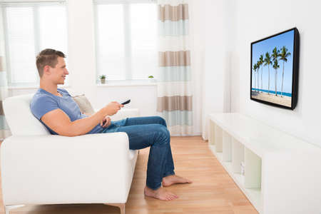 Young Man Sitting On Sofa Watching Television At Home Stock Photo