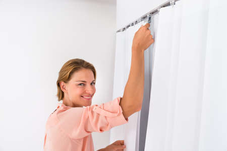 curtains: Young Woman Putting White Curtain At Home