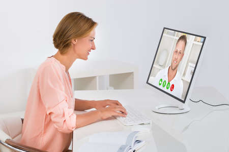 chatting: Young Happy Woman Videochatting On Computer At Desk Stock Photo