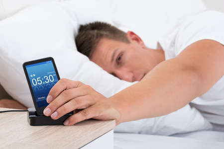 snoozing: Young Man On Bed Snoozing Alarm Clock On Cell Phone Screen