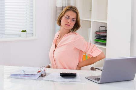 mujeres de espalda: Mujer joven que sufre de dolor de espalda mientras que el cálculo de impuestos en el escritorio Foto de archivo