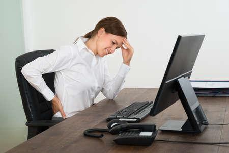 Jonge Zakenvrouw die lijden aan rugpijn en hoofdpijn bij Office
