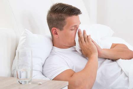 gripa: El hombre joven en la cama sopla su nariz en el pañuelo Foto de archivo