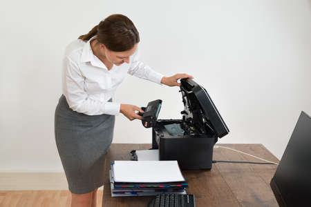 printer cartridge: Young Businesswoman At Desk Putting Laser Toner Cartridge In Printer