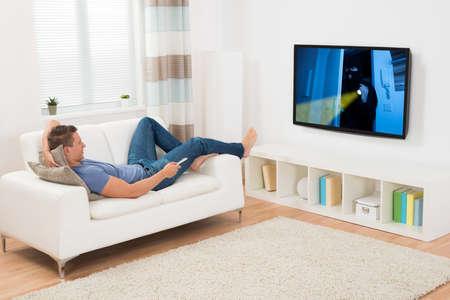 viendo television: Hombre Joven Pel�cula de observaci�n en la televisi�n en la sala de estar Foto de archivo