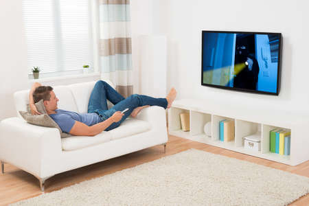 television: Young Man Watching Movie On Television In Living Room Stock Photo
