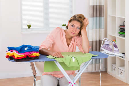 house cleaning: Young Bored Woman Sitting With Electric Iron And Clothes At Ironing Board